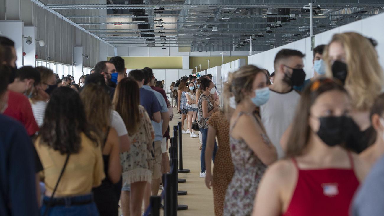 Varios jóvenes esperan en una fila para vacunarse