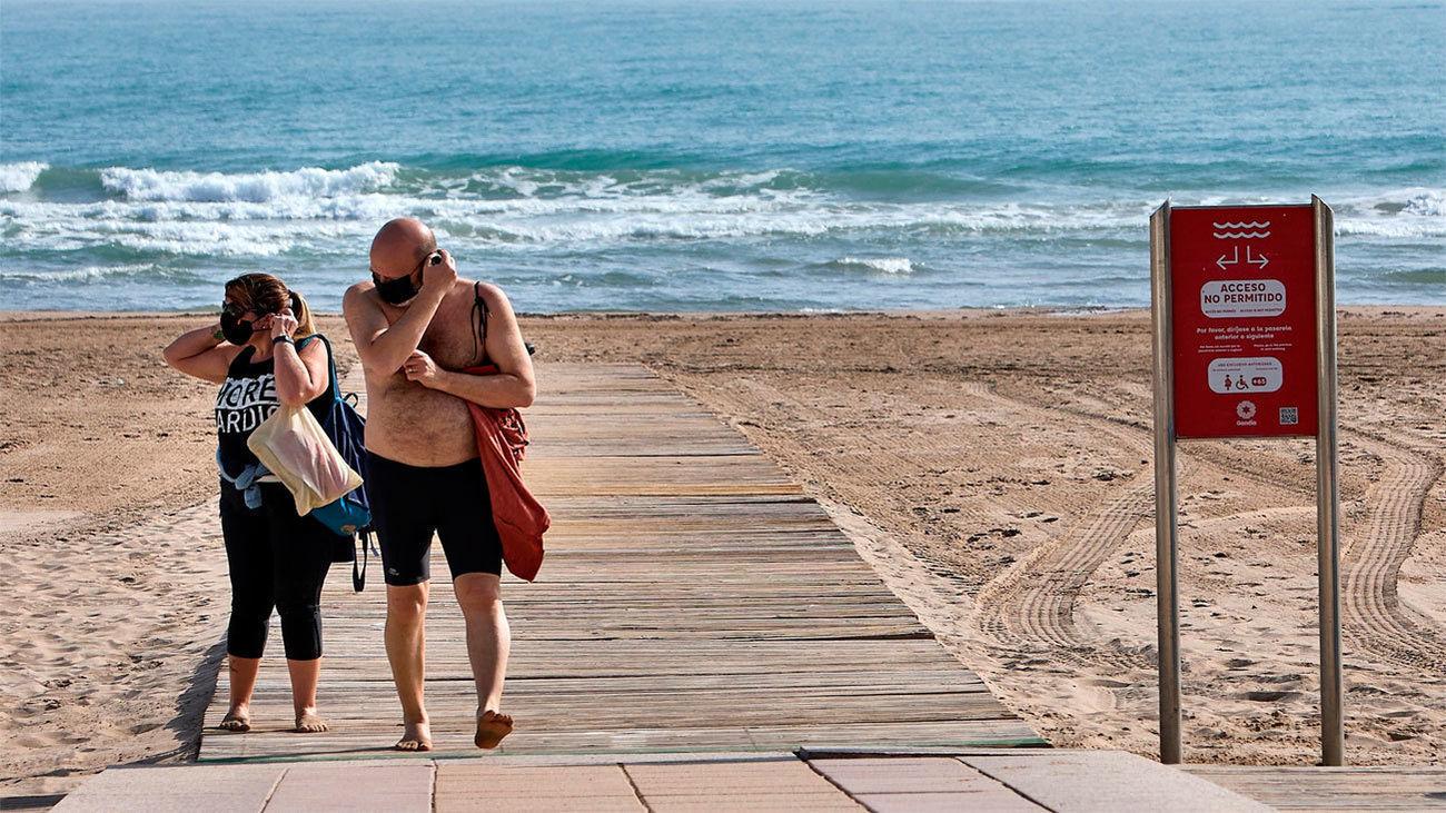 Dos personas se colocan las mascarillas mientras caminan por la plataforma de una playa