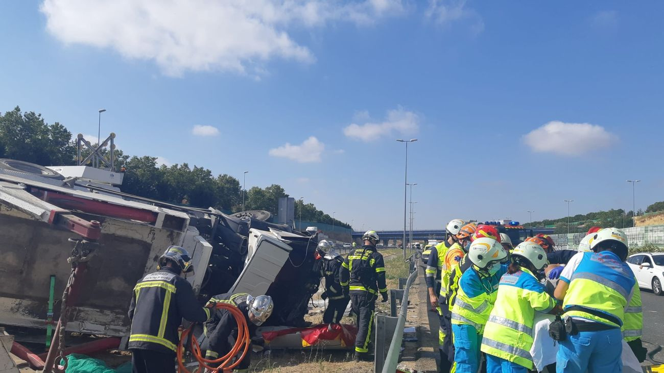 Los bomberos rescatan al conductor de un camión atrapado tras volcar en la M-50