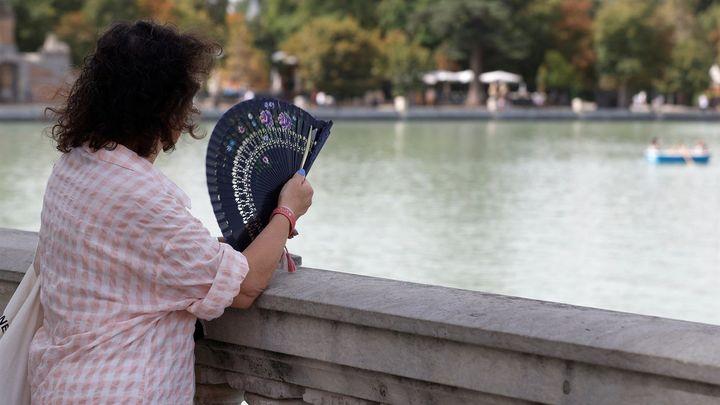 Quien tiene un abanico, tiene un tesoro. Imprescindible en estos días de ola de calor. Esta mujer aprovecha y usa el suyo en Madrid, mientras contempla a los valientes que reman bajo el ardiente sol en el lago del Retiro.