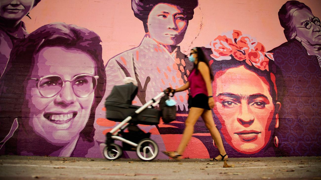 Una mujer camina junto al mural de las mujeres del barrio de Ciudad Lineal en Madrid