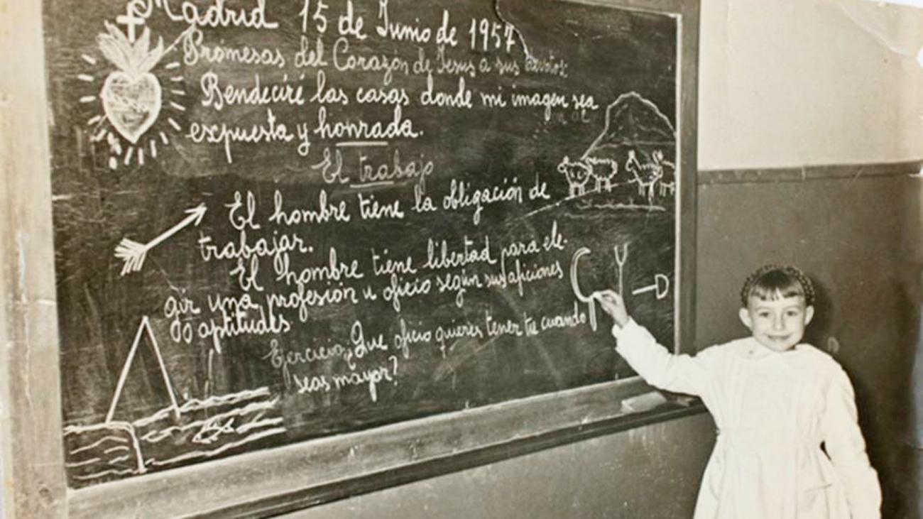 Una niña junto a la pizarra en un colegio de Usera, en 1957