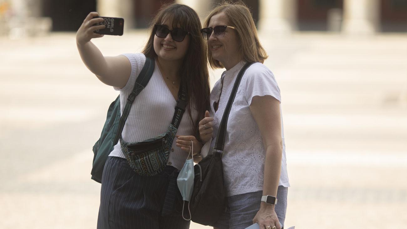 Dos turistas se hacen una foto en la Plaza Mayor