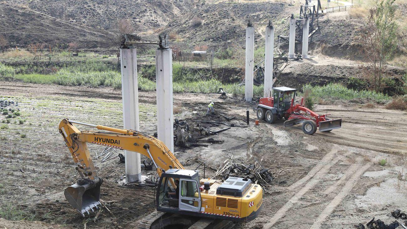 Maquinas retiran escombros y restos calcinados junto a los pilares de la pasarela destruida por el fuego