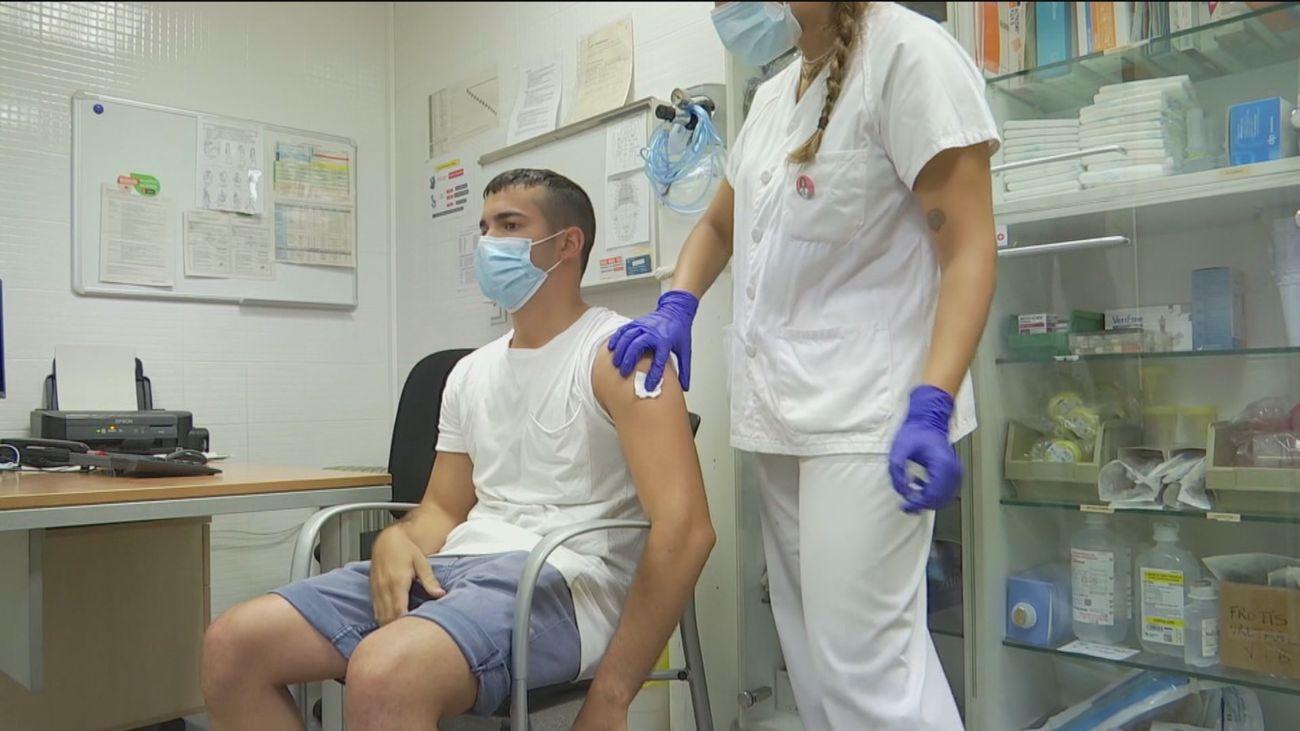 Una enfermera vacuna a un joven de Covid en Madrid