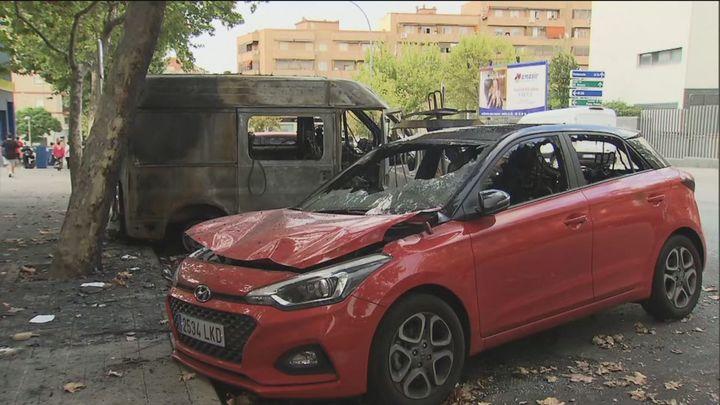 Coches calcinados tras la quema vandálica de contenedores en Puente de Vallecas