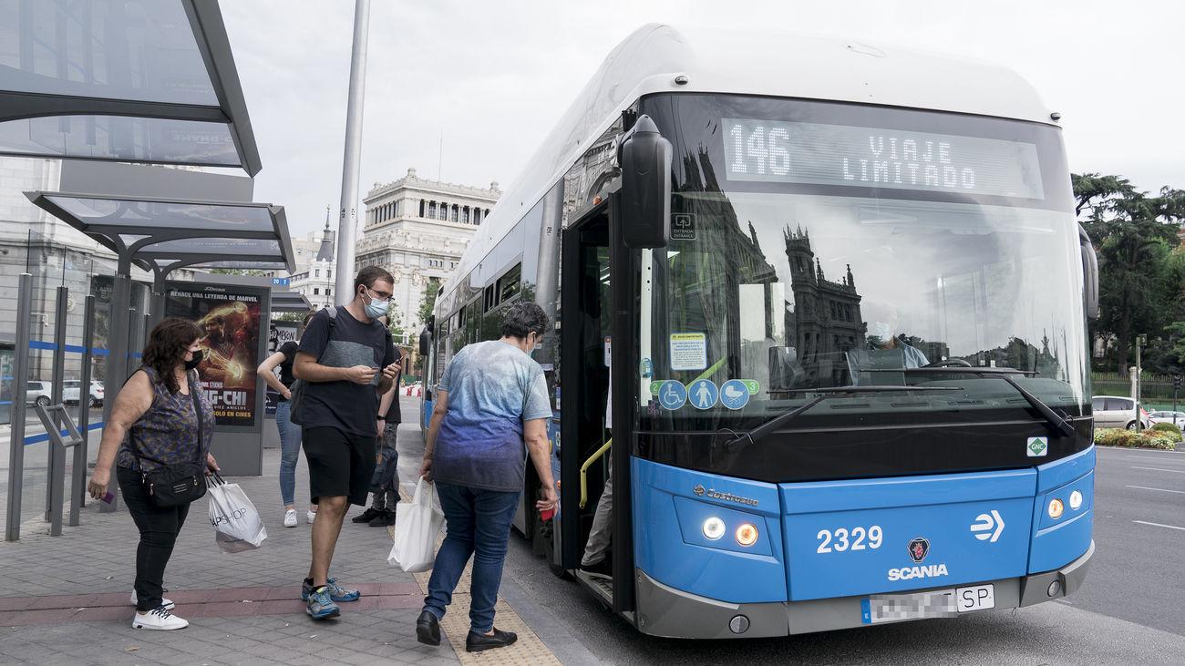 Varias personas suben un autobús de la EMT en la Plaza de Cibeles