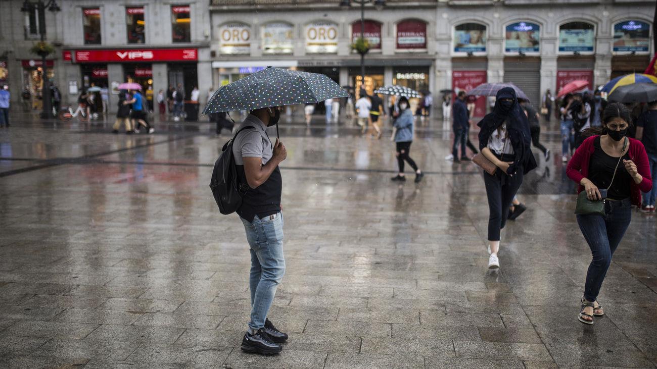 Varias personas se protegen de la lluvia en la Puerta del Sol