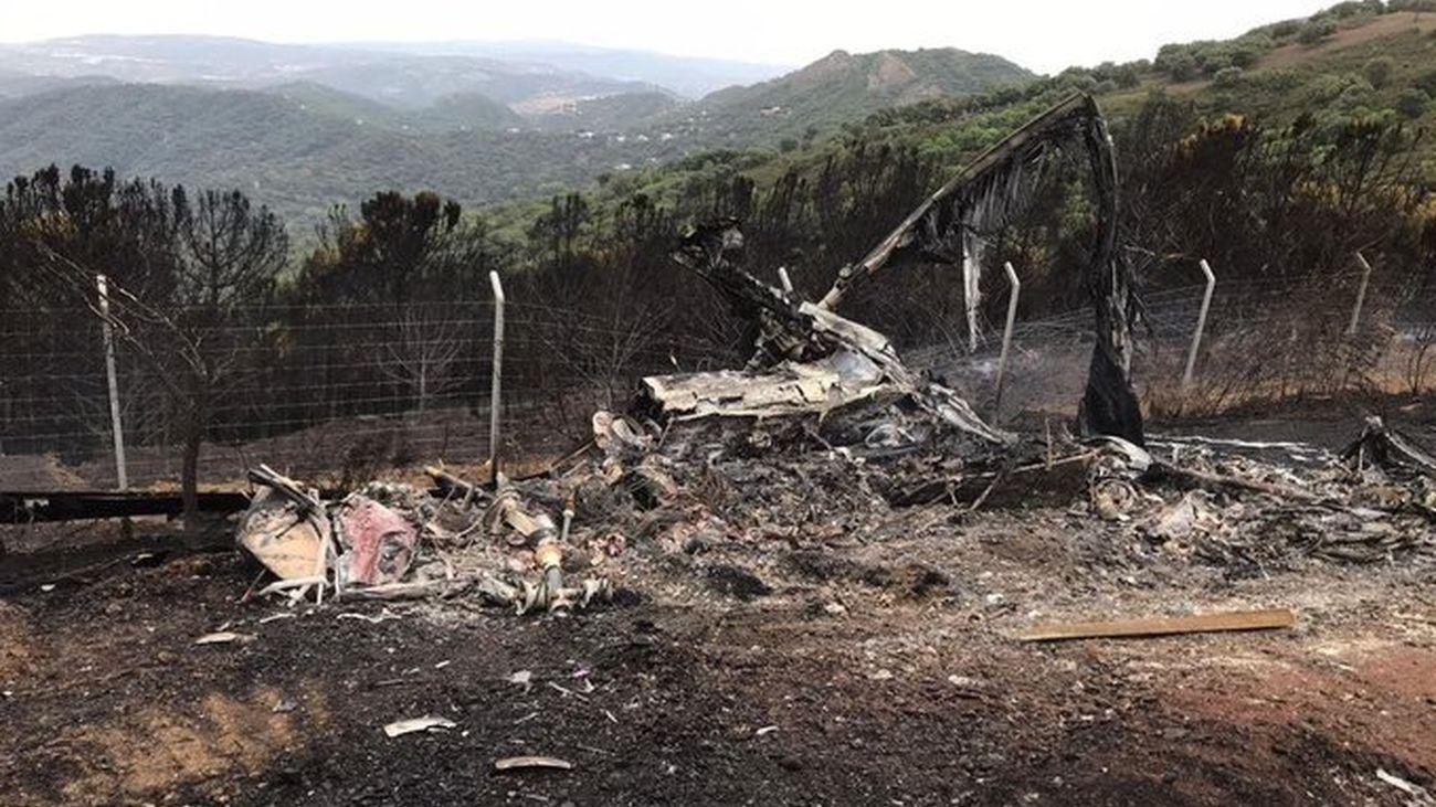 El helicóptero accidentado este lunes, calcinado por las llamas del incendio de Sierra Bermeja