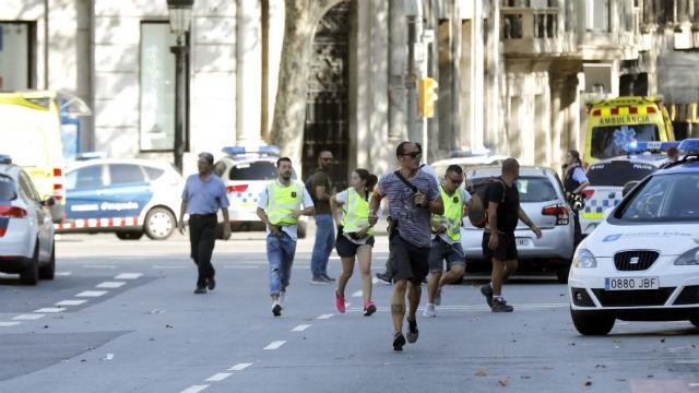 Gente en el lugar en el que una furgoneta ha atropellado esta tarde a varias personas que paseaban por las Ramblas de Barcelona
